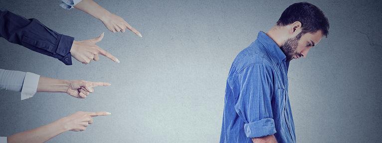 un homme triste montré du doigt