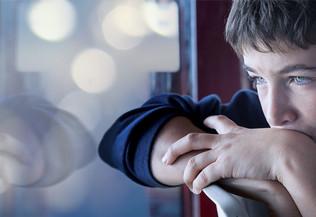 jeune garçon pensif, la tête sur les avant-bras - autisme