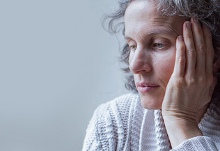 portrait d'une femme d'âge moyen, la tête sur la main, pensive