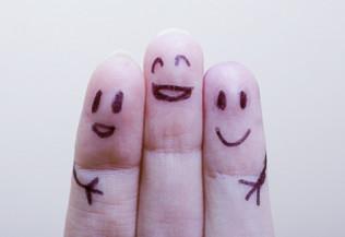 trois doigts sur lesquels sont dessinés des visages souriants - contact